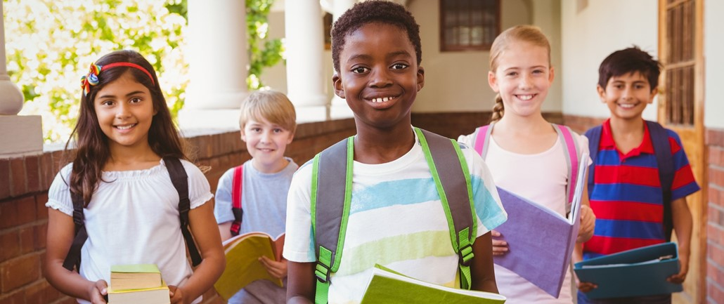 Children of different races holding notebooks