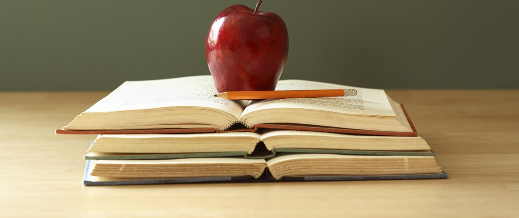 Red apple on top of three books